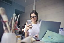 Free Woman In White T-shirt Holding Smartphone In Front Of Laptop Stock Images - 111364744
