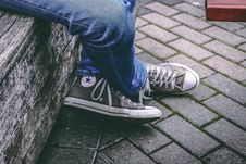 Free Person Wearing Brown Converse All-star High-top Sneakers And Blue Denim Jeans While Sitting On Bench Stock Photography - 111457342
