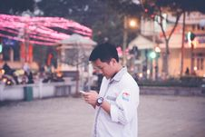 Free Focus Photography Of Man Wearing White Sports Shirt Holding Smartphone Near Buntings Royalty Free Stock Photo - 111545355
