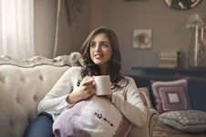 Free Woman Wearing White Top Drinking Beverage From White Ceramic Mug While Lying On Sofa Inside Well Lit Room Stock Photography - 111545602