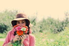 Free Woman Wearing Hat And Holding Flowers Surrounded By Plants Royalty Free Stock Photos - 111615108