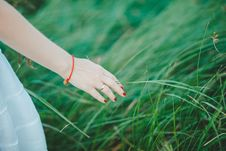 Free Woman Wearing White Skirt, Orange Bracelet, And Red Manicure Beside Green Grass Royalty Free Stock Images - 111615169