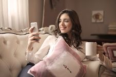 Free Woman In White Long-sleeved Shirt Holding Smartphone Sitting On Tufted Sofa Stock Photo - 111615240