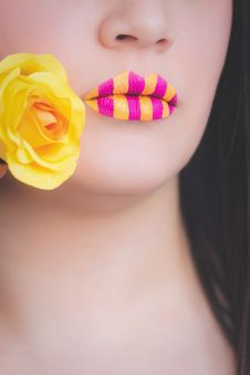 Free Woman Wearing Yellow And Pink Striped Lipstick Holding Yellow Rose Stock Photos - 111823723