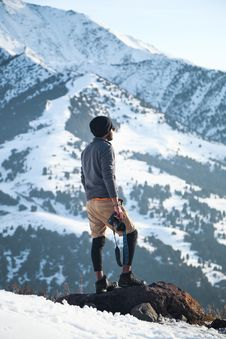 Free Man Wearing Gray Long-sleeved Shirt And Brown Shorts Holding Black Dslr Camera On Mountain Stock Images - 112089844