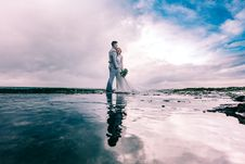 Free Man In Gray Dress Suit Jacket Embraces Woman Wearing Wedding Gown Stock Images - 112090034
