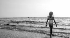 Free Grayscale Photo Of Girl Walking On Seashore With White Spaghetti Strap Top Royalty Free Stock Photo - 112090035