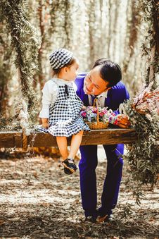 Free Selective Focus And Color Photography Of Man Looking At Her Girl Sitting On Garden Swing White Holding Bouquet Of Flower In Brown Royalty Free Stock Photo - 112090055