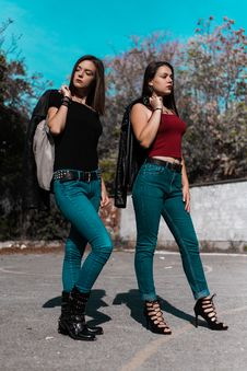 Free Woman In Black Cap-sleeved Shirt And Blue Denim Jeans Beside Woman In Red Spaghetti Strap Shirt Holding Black Leather Jacket At Da Stock Photo - 112184580