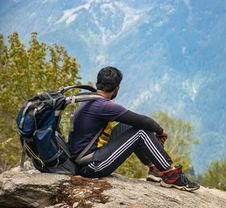 Free Man In Purple T-shirt With Blue Backpack Sitting On Gray Boulder Stock Photos - 112184653