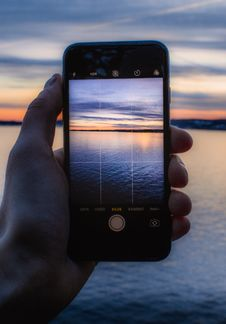 Free Person Holding Post-2014 Iphone Taking A Photo Of Body Of Water Stock Photos - 112301583