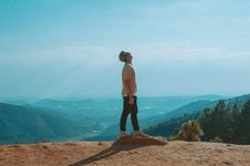 Free Man Wearing Beige Shirt And Black Pants Looking Up With Blue Sky And Mountains In The Background Stock Photography - 112301592