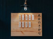 Free Kanji Printed Tags Hanged On Brown Wooden Board Lighted By Pendant Lamp Royalty Free Stock Image - 112301606