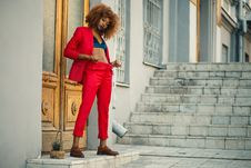 Free Woman In Black And Blue Sports Bra And Red Pants Standing In Front Of Brown Wooden Doors Near Gray Concrete Stairs Royalty Free Stock Images - 112308789