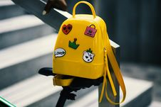 Free Yellow Backpack With Five Assorted Stickers On Grey Metal Stairway Rail Stock Image - 112455031