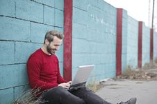 Free Man Leaning Against Wall Using Laptop Stock Image - 112455151