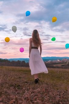 Free Woman In White Dress Looking At The Balloons Royalty Free Stock Image - 112455176