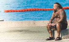 Free Man With Tattoos Sitting On Gray Concrete Floor Near Body Of Water Royalty Free Stock Images - 112669529