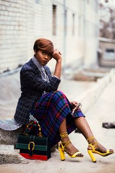 Free Woman Wearing Black And Grey Tattersall Blazer And Multicolored Plaid Skirt With Black Mesh Stocking And Yellow Chunky Heeled Sand Royalty Free Stock Photo - 112738575