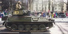 Free Two Soldiers Ride On Green Military Tank Surrounded With People Stock Images - 112738624
