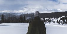 Free Man With Black Jacket And Grey Knit Cap Standing On White Snow Field Stock Image - 112738641