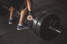 Free Man In Black Reebok Shoes About To Carry Barbell Royalty Free Stock Image - 112738666