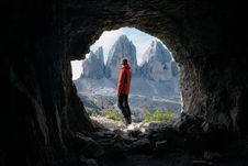 Free Man In Red Jacket Standing Outside Of Cave In Front Of Three Mountains Stock Photo - 112738670