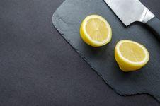 Free Sliced Lemon Beside Knife On Top Of Black Surface Stock Image - 112878161