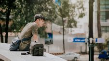 Free Man In Green And Beige Camouflage T-shirt Siting Beside Bag At Daytime Royalty Free Stock Photo - 112878285