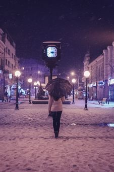 Free Person In White Long-sleeved Top And Black Pants Under Black Umbrella Standing Near Street Clock Royalty Free Stock Photo - 112942605