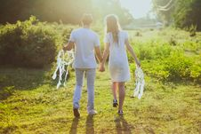Free Coupe With White Dress And Suit Holding A White Dreamcatcher While Walking On Green Grass Stock Photography - 113035942