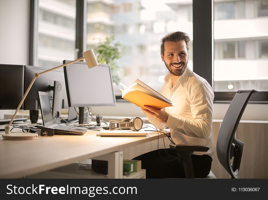 Photo of Man Holding a Book