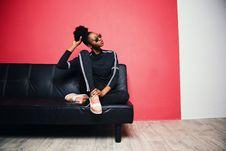 Free Woman With Black-and-white Sweater With Pants Sitting On Black Leather Sofa Beside Red Painted Wall Royalty Free Stock Images - 113143719