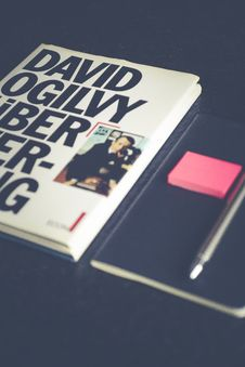Free David Ogilvy Book Lying Beside Black Leather Booklet Stock Images - 113232214