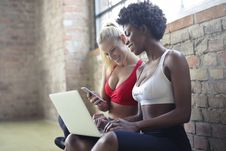 Free Two Women Wearing Red And White Sports Bras Sitting Near Brown Wall Bricks Royalty Free Stock Photo - 113294965