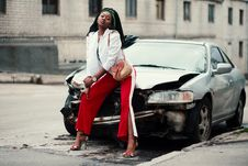Free Woman In White Open Cardigan And Red And White Pants Sitting On Damage White Car Royalty Free Stock Images - 113295209