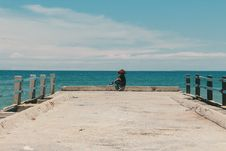Free Person Sitting On The Edge Of The Beach Dock Royalty Free Stock Photos - 113416818