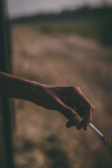 Free Person S Left Hand Holding White Cigarette Stick Stock Image - 113416961