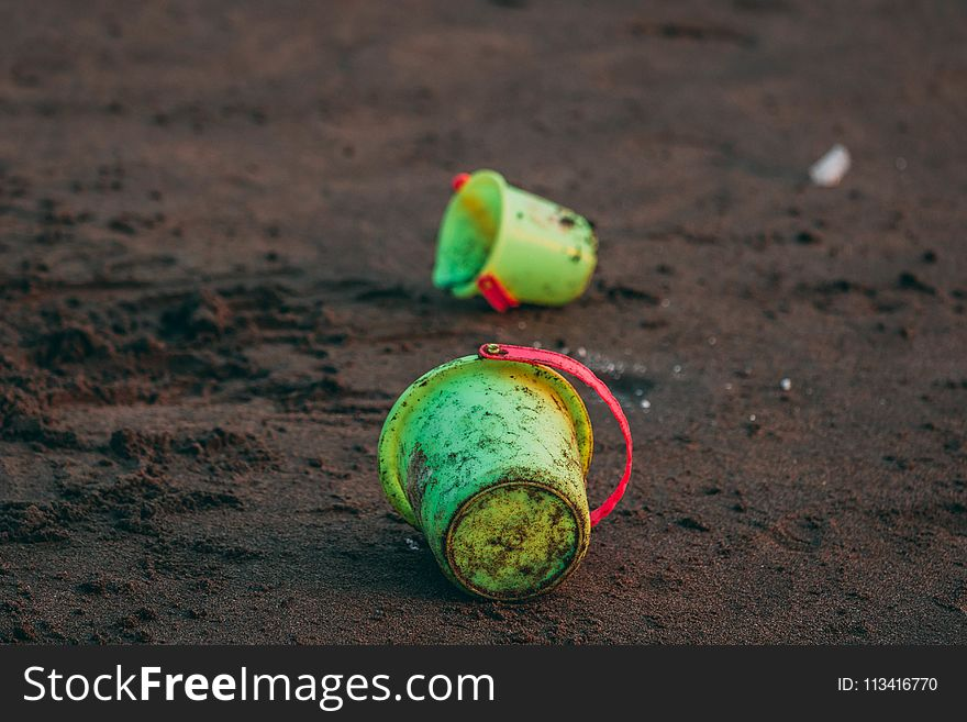 Two Green Pails on Ground