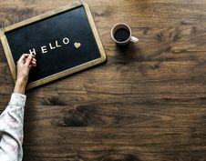 Free Person S Hand On Black Board With Hello Text Beside Brown Mug Royalty Free Stock Photography - 113472677