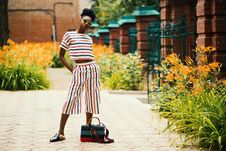 Free Woman Wearing White, Black, And Red Striped Crew-neck T-shirt With Matching Pants Standing Outside Beside Black Leather 2-way Bag Stock Images - 113473014
