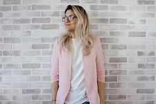 Free Woman In Pink Cardigan And White Shirt Leaning On The Wall Stock Image - 113473031