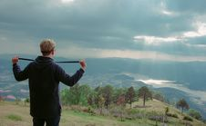 Free Man Wearing Hoodie Standing On Mountain Under Cloudy Sky Stock Photography - 113540082