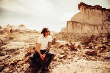 Free Man In White Crew-neck T-shirt And Black Pants Sitting On Boulder Near Cliff Stock Photo - 113641920