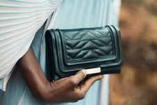 Free Person Holding Quilted Black Leather Clutch Bag Stock Image - 113641941