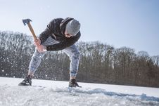 Free Man Wearing Black Hooded Jacket, Gray Knit Cap, Gray Pants, And Black Shoes Holding Brown Handled Axe While Bending On Snow Stock Images - 113808974