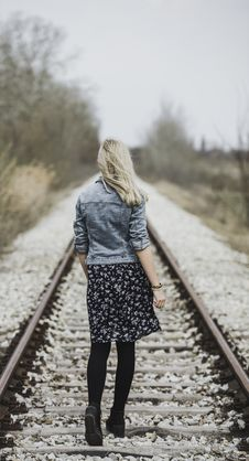 Free Woman In Blue Denim Jacket, Black Leggings And Black And White Dress Walking On Train Rail Royalty Free Stock Images - 113809109
