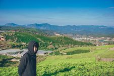 Free Man Wearing Hoodie Taking Picture With Mountain And Field Photography Stock Images - 113809164