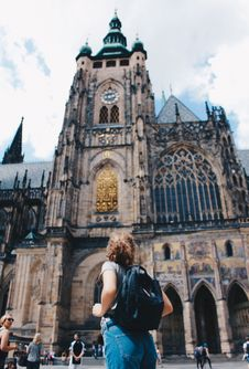 Free Woman Wearing Backpack And Grey Shirt Near Brown Church Stock Image - 113851401