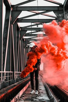 Free Man In Black Jacket Holding Red Smoke On Metal Bridge Royalty Free Stock Images - 113907749